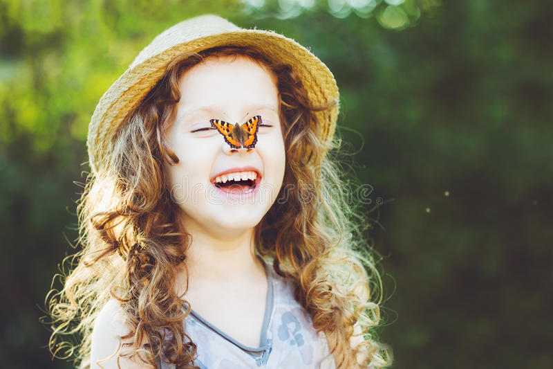 Ragazza riccia di risata con una farfalla sulla sua mano Childhoo felice immagine stock