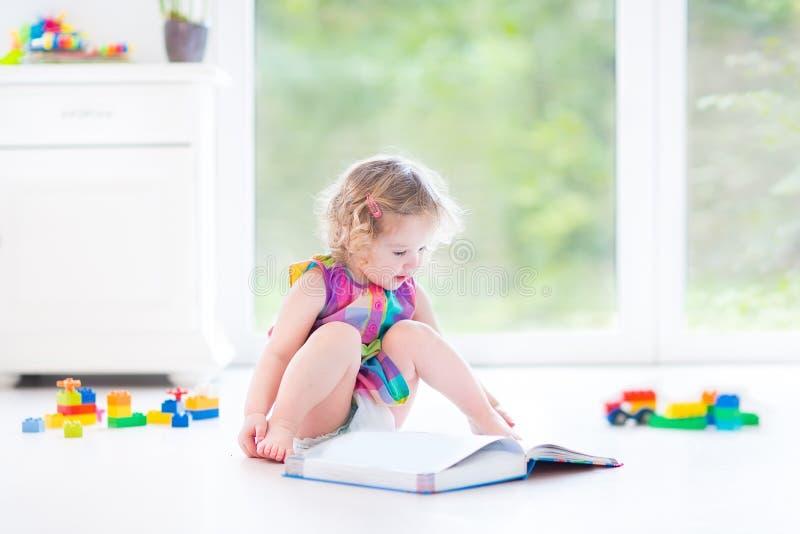 Ragazza riccia divertente del bambino che legge un libro che si siede sul pavimento fotografie stock
