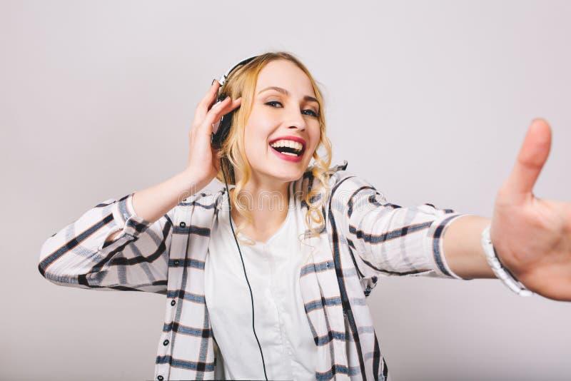 Ragazza riccia felice in camicia a strisce che sorride e che balla mentre canzone favorita d'ascolto in cuffie Ritratto del primo fotografie stock