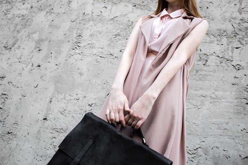 Ragazza rossa dei capelli nello sguardo rosa, con la borsa di cuoio nera, posa sui precedenti di concrette fotografia stock
