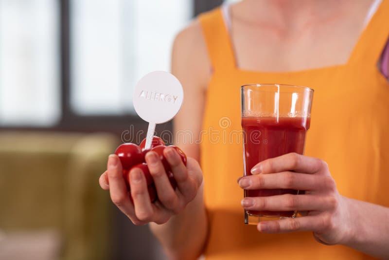 Ragazza scarna nella cima luminosa che tiene i pomodori e vetro di succo fotografie stock libere da diritti