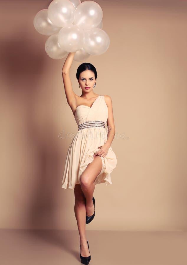 Ragazza sensuale con capelli scuri in vestito beige elegante che tiene i palloni bianchi fotografia stock