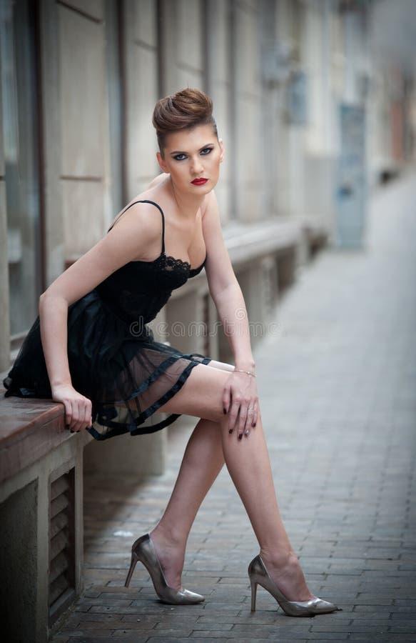 Ragazza sensuale con le gambe, il vestito lungo dal nero di short ed i tacchi alti sedentesi sul banco Minigonna d'uso e tacco al immagine stock