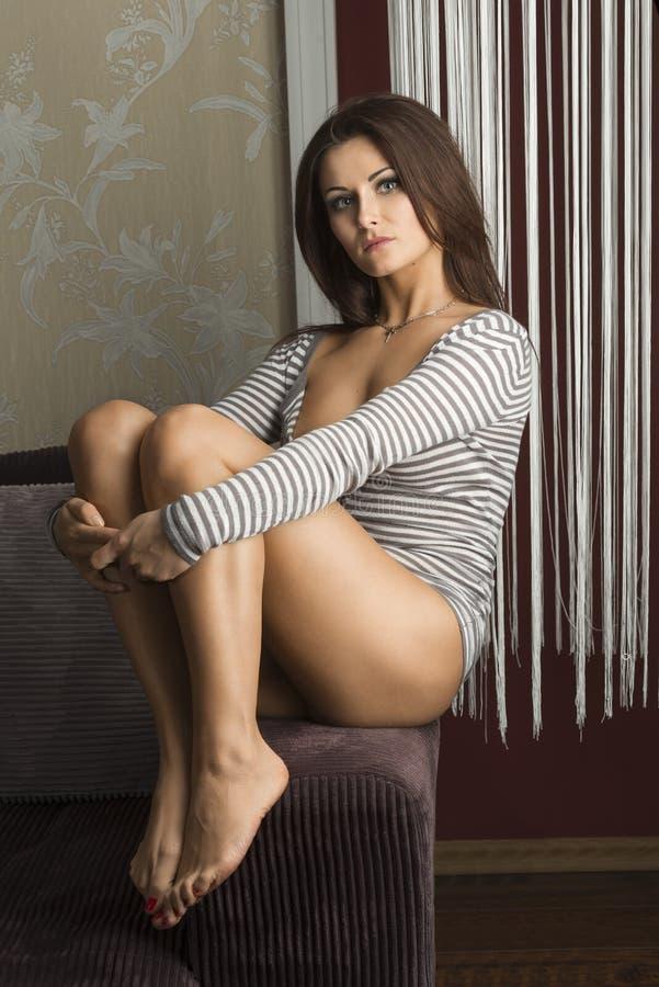Ragazza sensuale, sedentesi sul sofà, fotografia stock libera da diritti