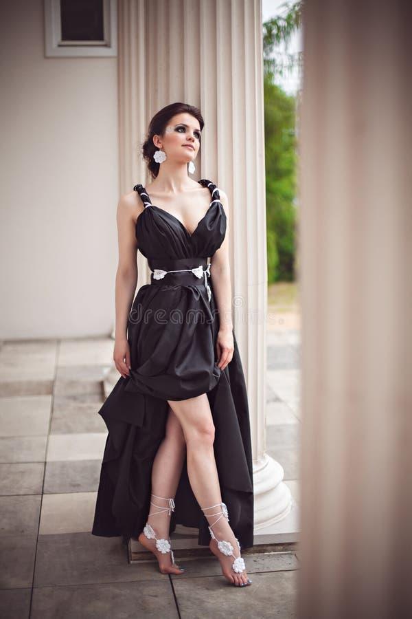 Ragazza sensuale in vestito nero lungo alla colonna fotografie stock libere da diritti