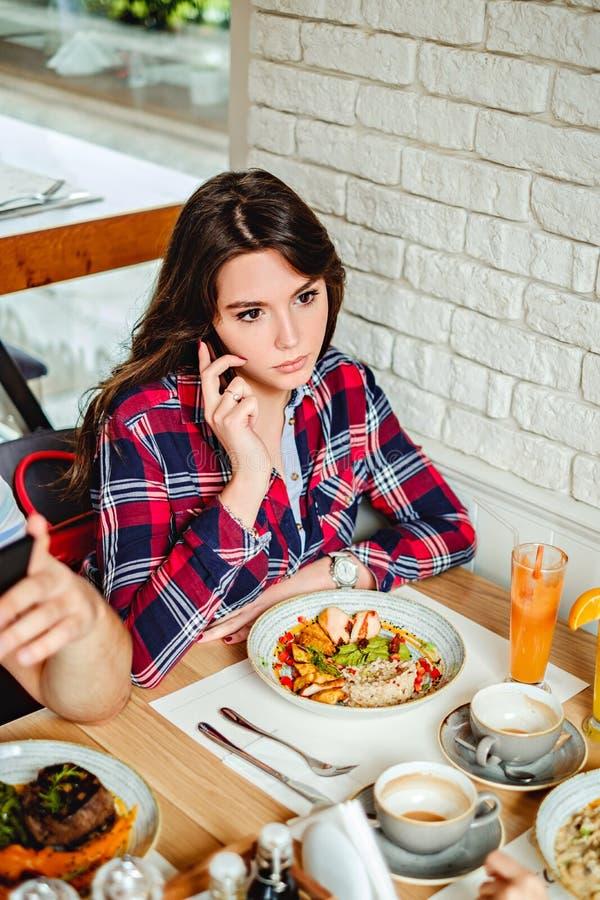 Ragazza seria che fa una telefonata al ristorante immagine stock