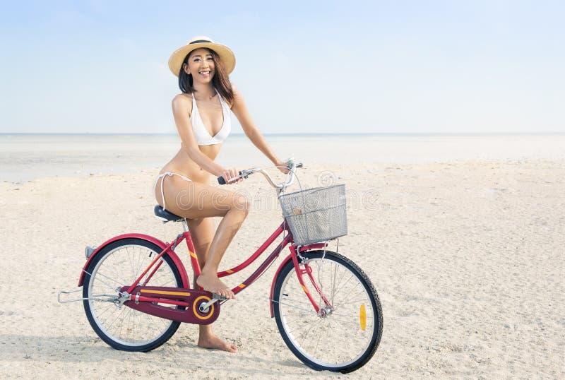 Ragazza sexy asiatica con la bicicletta di guida del bikini e del cappello sulla spiaggia fotografia stock