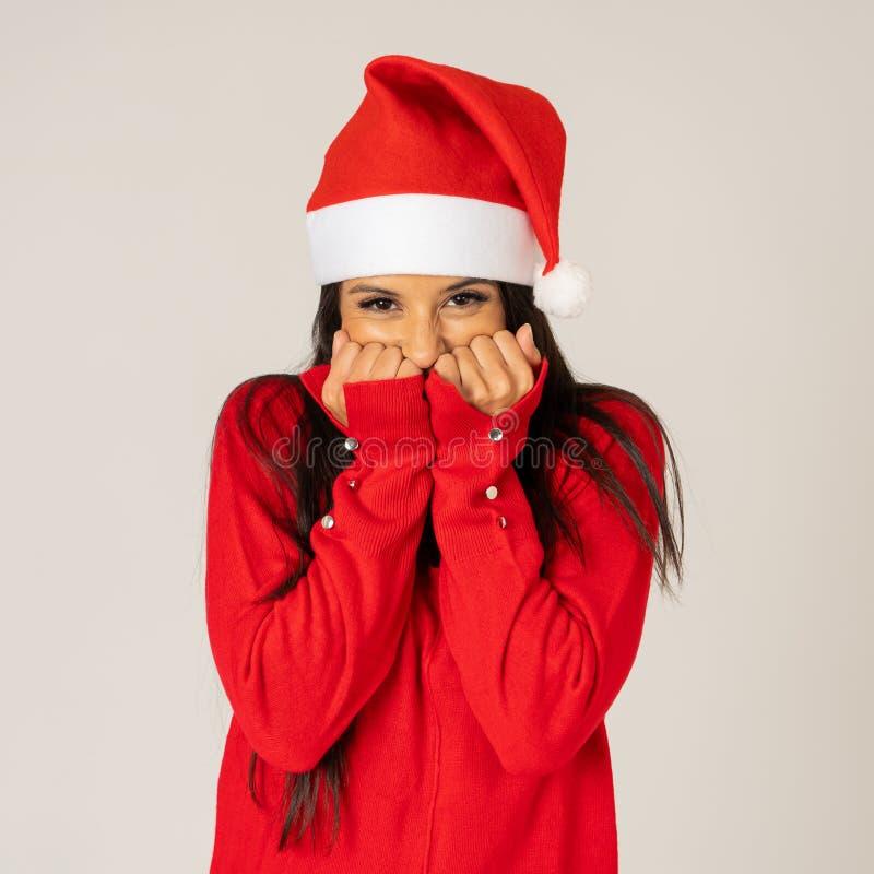 Ragazza sexy attraente che posa in vestito rosso e cappello di Santa isolati su fondo grigio fotografia stock