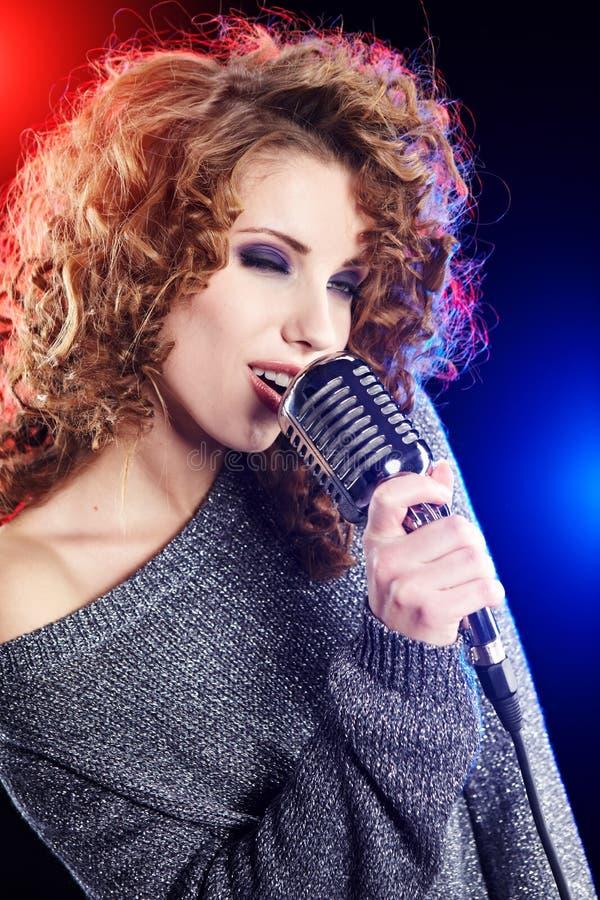 Ragazza sexy che canta nel retro mic immagine stock