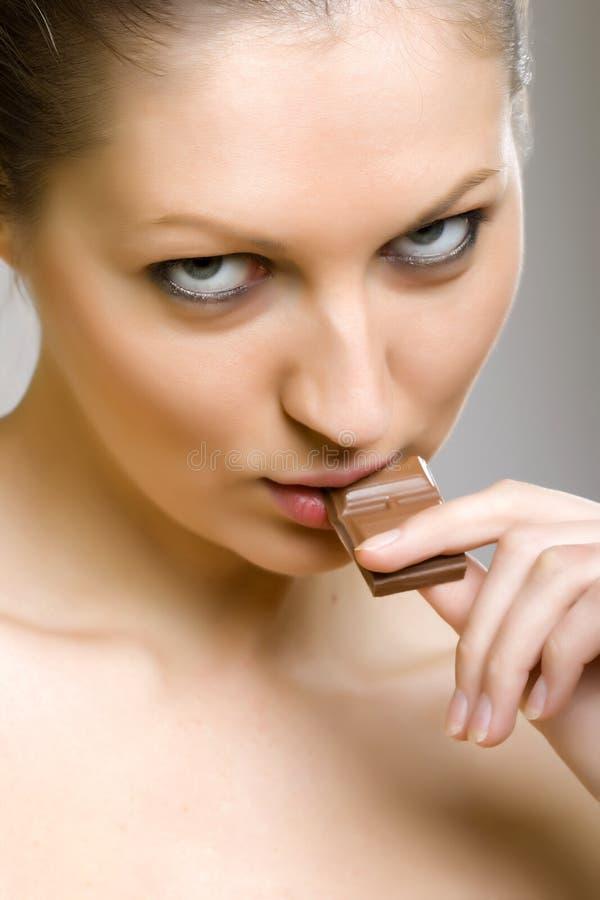 Ragazza sexy che mangia cioccolato fotografie stock libere da diritti