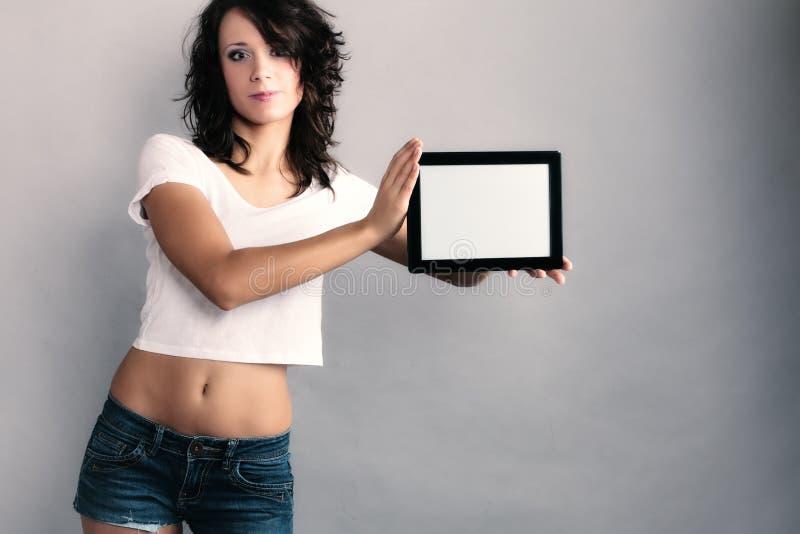 Ragazza sexy che mostra lo spazio della copia sul touchpad della compressa immagini stock