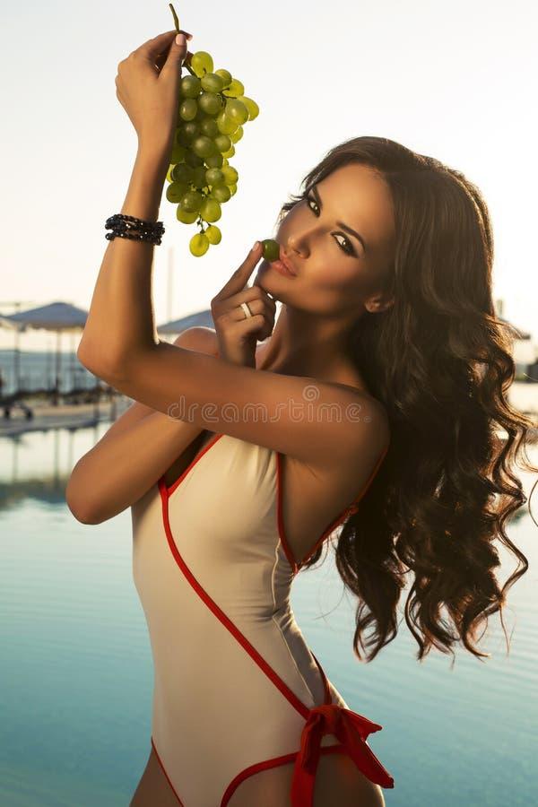 Ragazza sexy che posa accanto ad una piscina con il mazzo di uva immagine stock libera da diritti