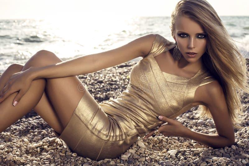 Ragazza sexy con capelli biondi in vestito dall'oro che posa sulla spiaggia fotografia stock
