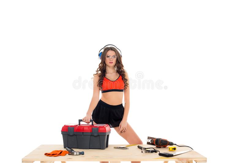 ragazza sexy in cuffie protettive che stanno alla tavola di legno con la cassetta portautensili e l'attrezzatura, fotografie stock