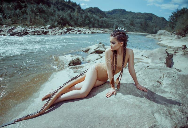 Ragazza sexy del drago del fiume L'immagine insolita di una sirena con una coda della lucertola che riguarda le scale e le punte  fotografia stock