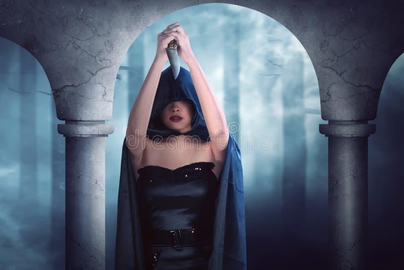 Ragazza sexy della strega con il coltello tagliente che pensa al sacrificio immagini stock libere da diritti