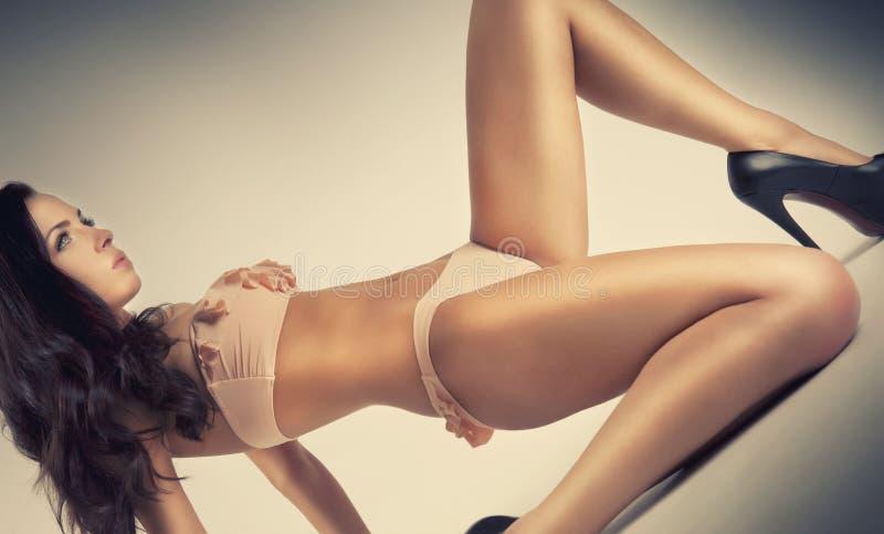 Ragazza sexy di posa di fascino che si trova sul pavimento immagine stock