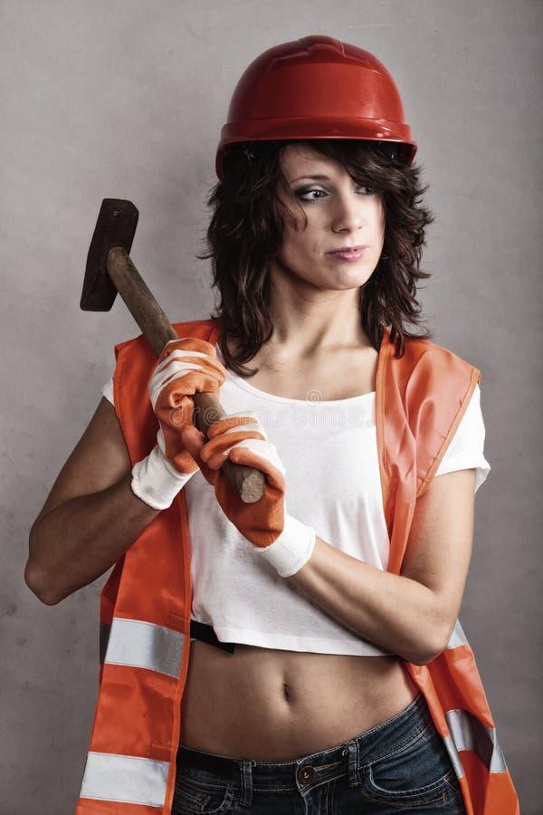 Ragazza sexy in strumento del martello della tenuta del casco di sicurezza immagine stock