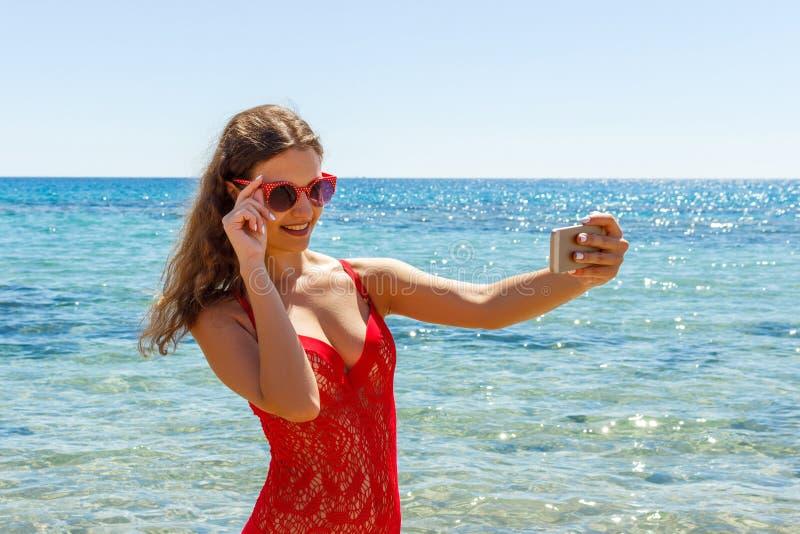 Ragazza sexy su una spiaggia con l'espressione sorpresa che esamina telefono e che prende selfie fotografie stock libere da diritti