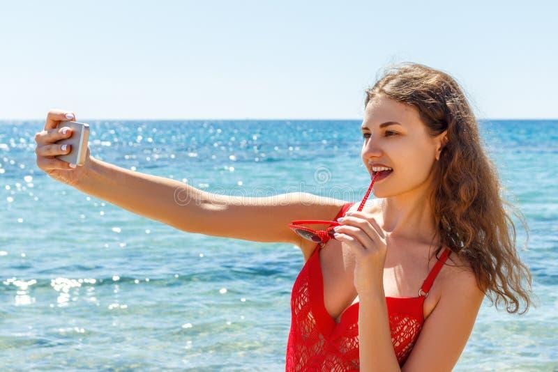 Ragazza sexy su una spiaggia con l'espressione sorpresa che esamina telefono e che prende selfie immagini stock