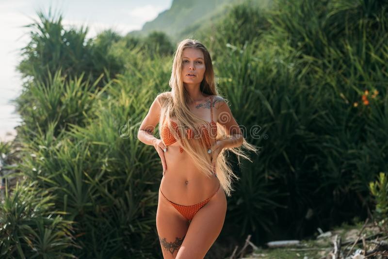 Ragazza sexy su una spiaggia selvaggia in un costume da bagno separato Il modello con capelli biondi lunghi spessi si segna e sot immagini stock libere da diritti
