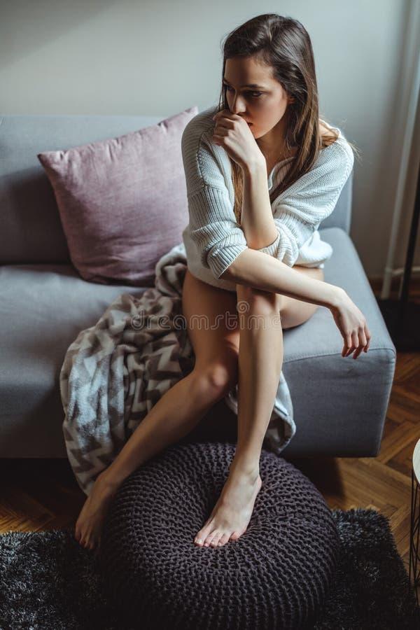 Ragazza sexy triste che si siede su un sofà da solo fotografie stock