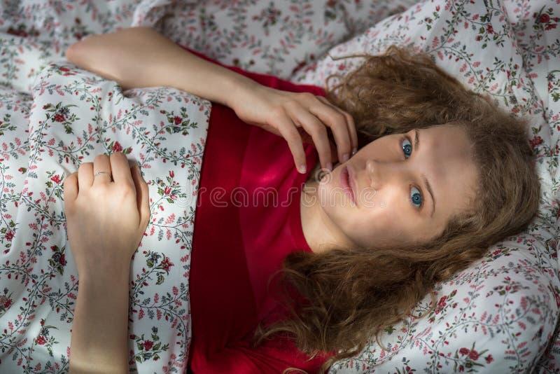 Ragazza sola civettuola a letto immagini stock