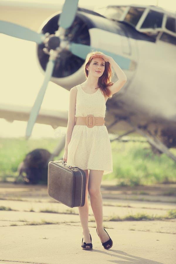 Ragazza sola con la valigia all'aeroplano vicino. immagini stock libere da diritti