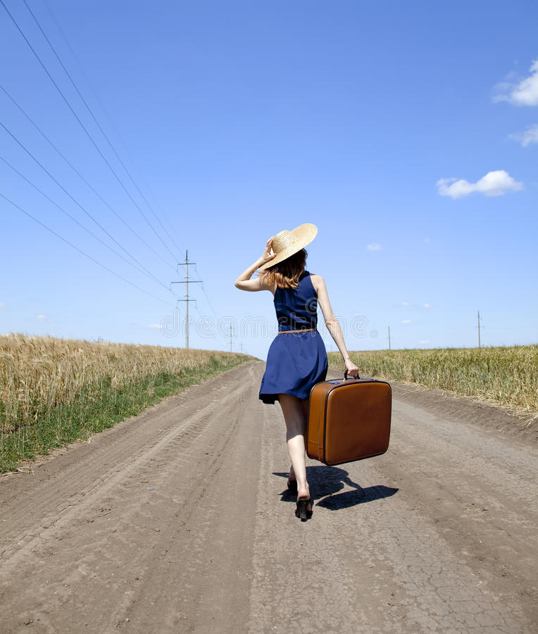 Ragazza sola con la valigia alla strada campestre. immagini stock libere da diritti