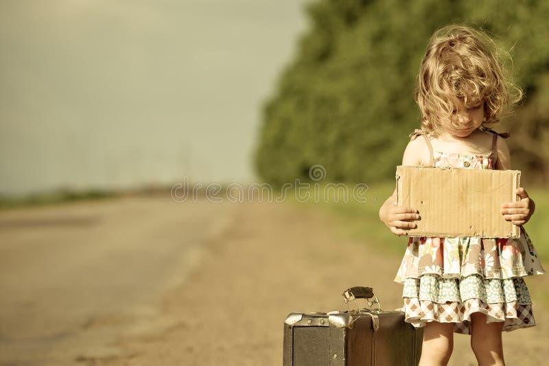 Ragazza sola con la valigia che si leva in piedi circa la strada immagini stock libere da diritti