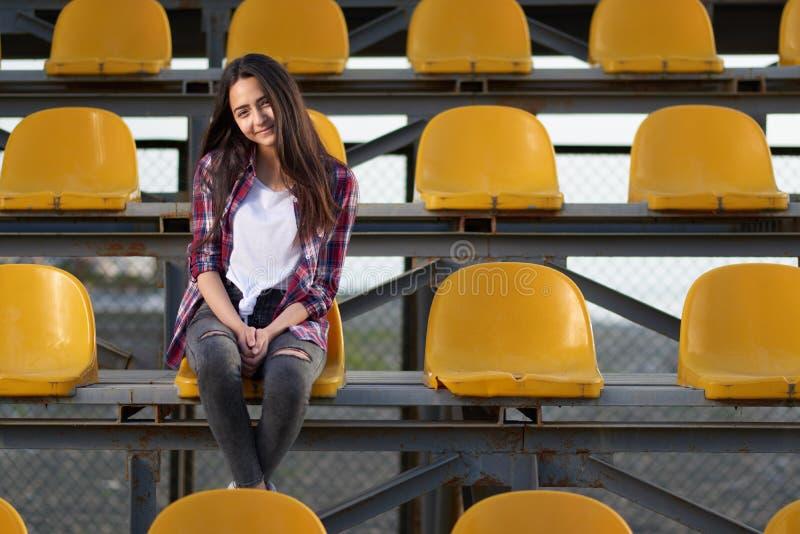 Ragazza sola della ragazza pon pon che si siede dolce nei supporti e nei sorrisi fotografia stock libera da diritti