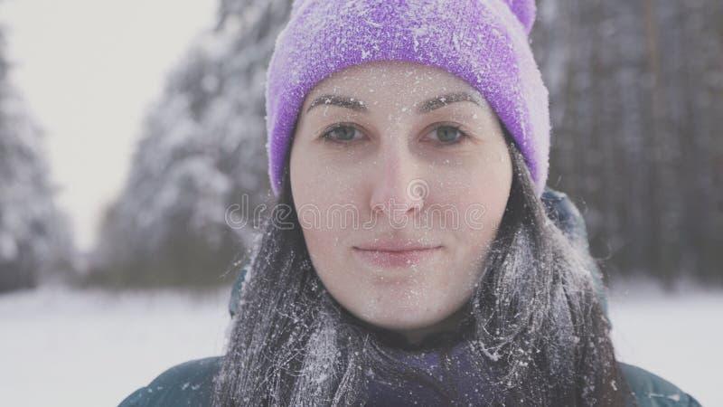 Ragazza sola nel legno che sorride esaminando la macchina fotografica, coperta di neve dopo una tempesta della neve immagine stock