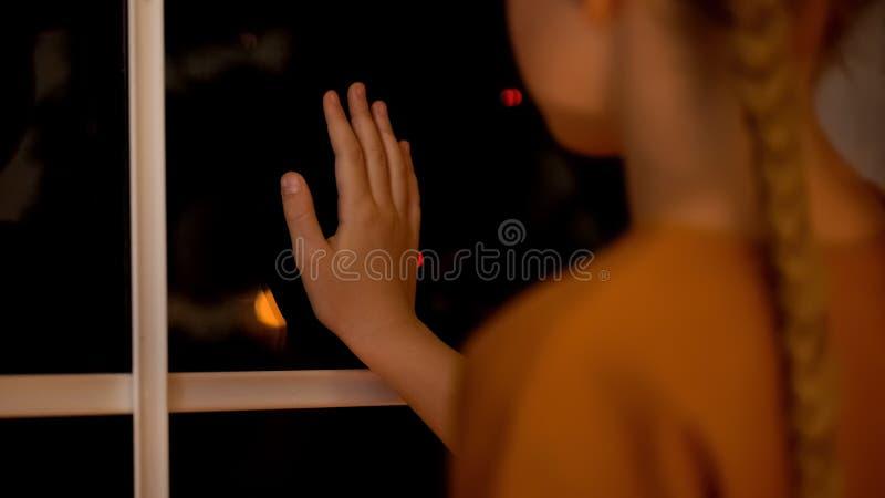 Ragazza sola triste che guarda attraverso la finestra, genitori aspettanti nella casa orfana, adozione immagini stock