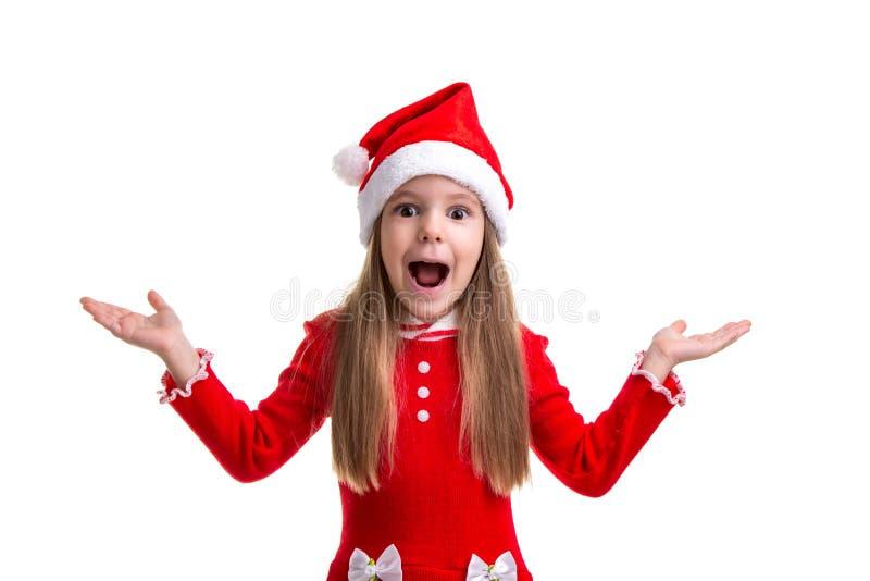 Ragazza sorpresa e colpita di natale che porta un cappello di Santa isolato sopra un fondo bianco immagine stock libera da diritti