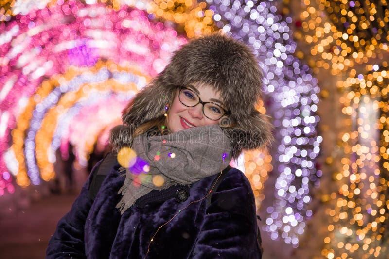 Ragazza sorridente allegra allegra del ritratto in un cappuccio della pelliccia di inverno contro lo sfondo di illuminazione di n immagini stock libere da diritti