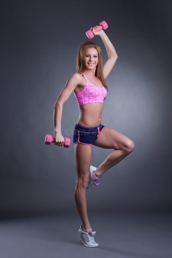 Ragazza sorridente atletica che posa con le teste di legno fotografia stock libera da diritti