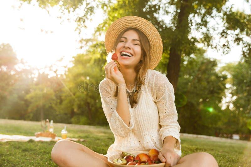 Ragazza sorridente in cappello di estate che ha un picnic al parco, sedentesi su un'erba fotografia stock