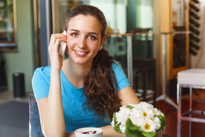 Ragazza sorridente che beve un cappuccino ed avere una chiamata fotografia stock