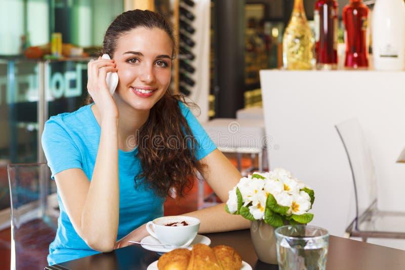 Ragazza sorridente che beve un cappuccino ed avere una chiamata con il suo MP immagini stock