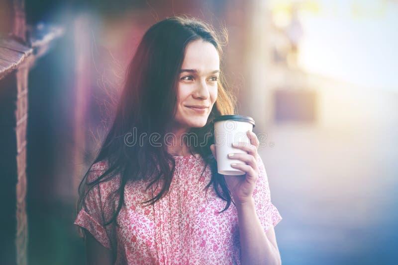 Ragazza sorridente che cammina con il caffè di mattina immagini stock