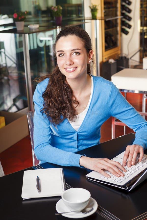 Ragazza sorridente che ha una pausa caffè e che lavora ad un computer fotografia stock libera da diritti