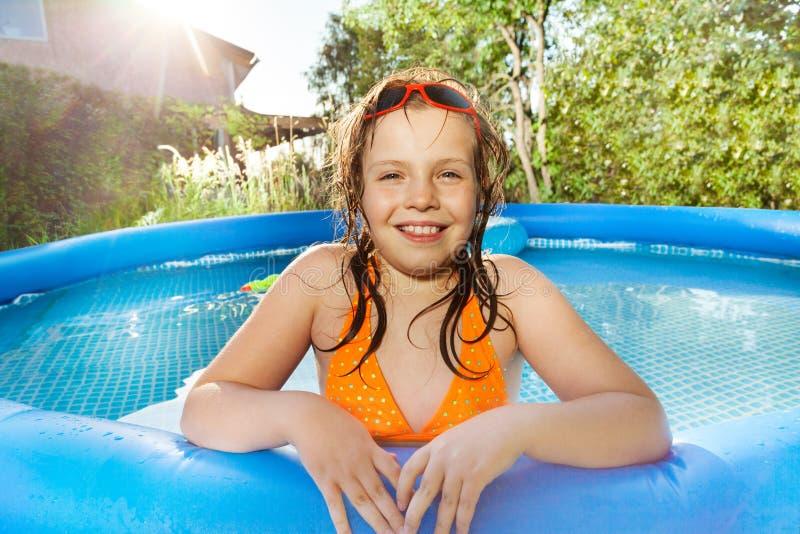 Ragazza sorridente che posa nella piscina immagini stock