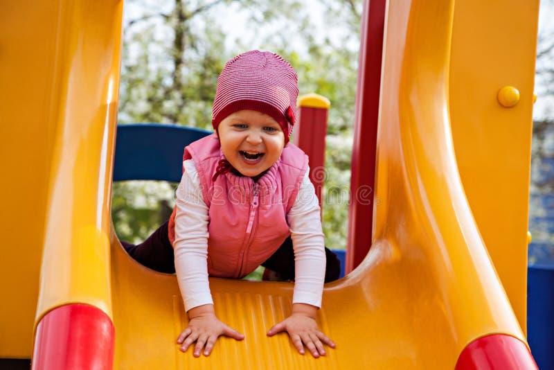 Ragazza sorridente che si siede allo scorrevole giallo fotografie stock libere da diritti