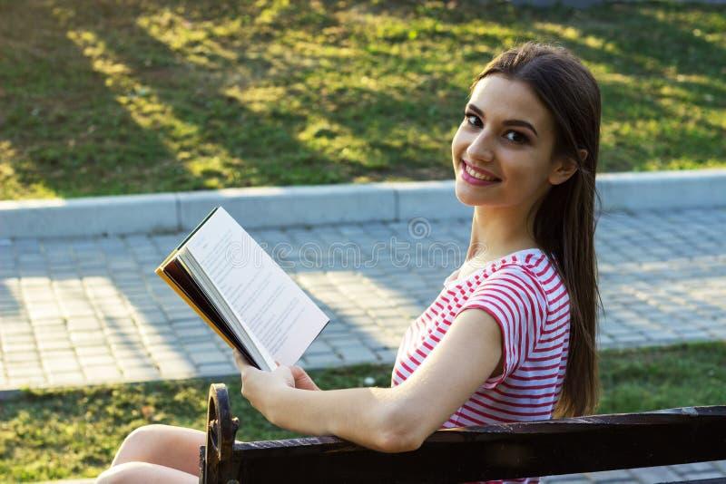 Ragazza sorridente che si siede su un banco di legno, leggente un libro I giri graziosi della ragazza si dirigono indietro durant fotografia stock libera da diritti