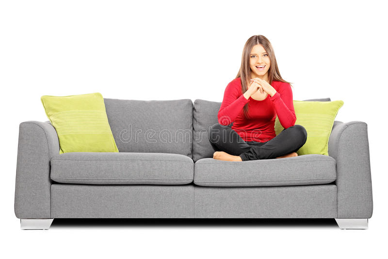 Ragazza sorridente che si siede su un sofà e sull'esame della macchina fotografica fotografia stock
