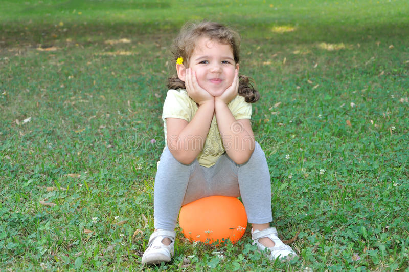 Ragazza sorridente che si siede su una palla fotografia stock