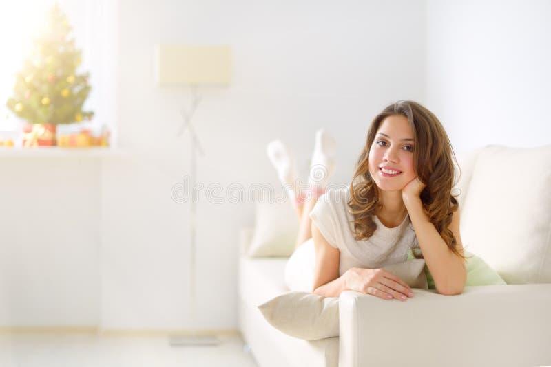 Ragazza sorridente che si siede sul sofà immagine stock libera da diritti