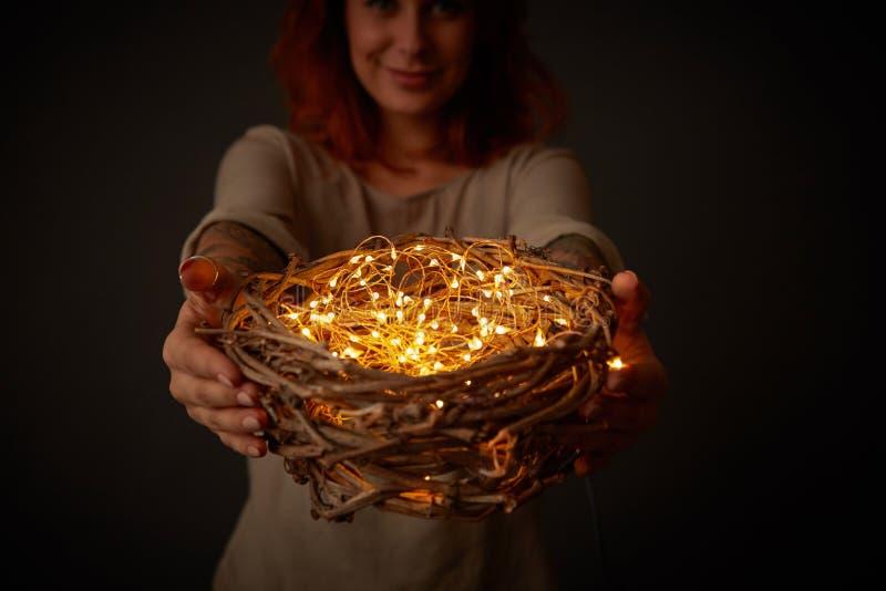 Ragazza sorridente che tiene una corona dei ramoscelli con le luci gialle intorno ad un fondo nero immagini stock