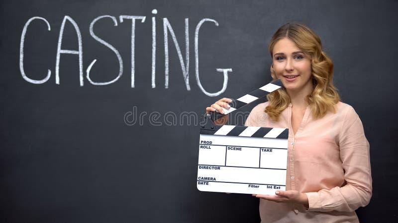 Ragazza sorridente che usa il cartellone per il casting, le audizioni cinematografiche, il talento dell'attore immagini stock libere da diritti
