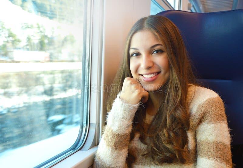 Ragazza sorridente che viaggia in treno con il paesaggio della neve di inverno dalla finestra che esamina la macchina fotografica immagini stock libere da diritti